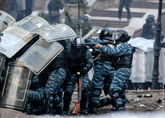 A riot police officer aims his weapon during clashes with pro-European integration protesters in Kiev
